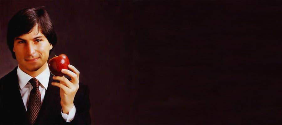 Молодой Стив Джобс в костюме с бордовым галстуком